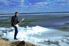 Der Kerl mit der Gitarre auf dem Strand in der Jacke, auf Eis Stockbild
