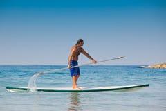 Der Kerl mit einem Ruder auf einem Surfbrett. Stockfoto