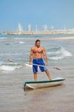 Der Kerl mit einem Ruder auf einem Surfbrett. Stockfotografie