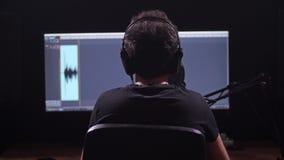 Der Kerl notiert den Ton seiner Stimme Tonstudio Rekordniveaus sind auf dem Schirm sichtbar 4K langsames MO stock video footage