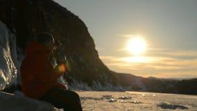Der Kerl raucht vape bei Sonnenuntergang im Winter stock footage