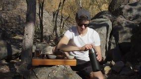 Der Kerl sitzt durch das Steinbewegen stock video footage