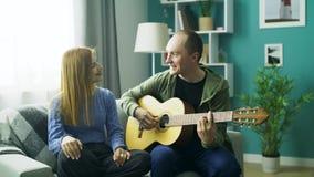 Der Kerl spielt seine Freundin auf der Gitarre im Wohnzimmer stock video