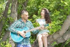 Der Kerl spielt seine geliebte Gitarre Mädchen mit Vergnügen mit geschlossenen Augen hören, sitzend auf einem Baum stockfoto