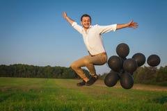Der Kerl springend mit schwarzen Ballonen auf dem Gebiet Lizenzfreies Stockfoto