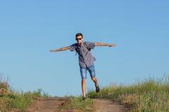 Der Kerl springend zur Spitze auf der Straße, Reisekonzept lizenzfreies stockfoto