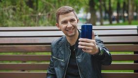 Der Kerl steht auf Videoschw?tzchen ?ber Smartphone in Verbindung lizenzfreie stockfotografie