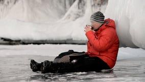 Der Kerl trinkt Tee auf Eis stock video footage