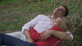Der Kerl umarmt ein Mädchen in einer Hängematte stock footage