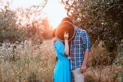 Der Kerl und das Mädchen, die auf Natur, Umarmung und Kuss unter dem Deckmantel eines breiten Hutes stehen Lizenzfreie Stockfotos