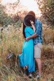 Der Kerl und das Mädchen, die auf Natur, Umarmung und Kuss unter dem Deckmantel eines breiten Hutes stehen Stockfotos