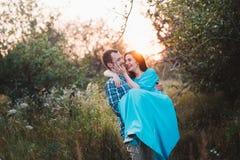 Der Kerl und das Mädchen, die auf Natur, Umarmung und Kuss unter dem Deckmantel eines breiten Hutes stehen Stockbild
