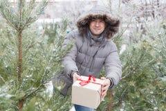 Der Kerl unter Tannenbäumen mit einem Geschenk Lizenzfreie Stockfotos