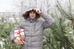 Der Kerl unter Tannenbäumen mit einem Geschenk Stockfotos