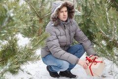 Der Kerl unter Tannenbäumen mit einem Geschenk Stockbilder