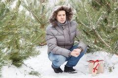 Der Kerl unter Tannenbäumen mit einem Geschenk Lizenzfreies Stockfoto