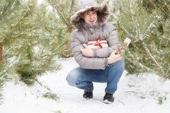Der Kerl unter Tannenbäumen mit einem Geschenk Stockfoto