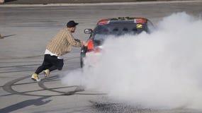 Der Kerl versucht, ein Sportauto zu erreichen Stockbild