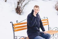 Der Kerl in der Winterjacke spricht am Telefon auf der Straße stockfotografie