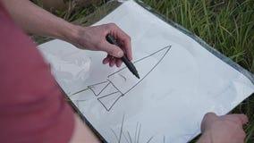 Der Kerl zeichnet einen Markierungsplan, um eine selbst gemachte Papprakete zu errichten Nahaufnahme des Gesichtes und der Hände stock footage