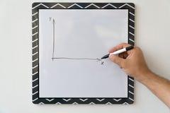 Der Kerl zeichnet einen Zeitplan auf einem weißen Brett Männliche Hand mit einer Markierung auf einem Hintergrund des weißen Bret Stockfotografie