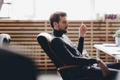 Der Kerl, der in der zuf?lligen B?roartkleidung gekleidet wird, sitzt in einem B?rostuhl am Schreibtisch im modernen B?ro stockfoto