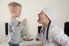 Der Kind-` s Doktor überprüft Patienten in seinem Büro Glückliche Kinder lieben einen guten Kinderarzt sehr Schließen Sie oben vo stockbild