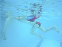 Der Kind-` s Fuß und der Erwachsene unter Wasser im Pool Stockbilder