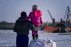 Der Kind-` s Vater steht auf den Banken des Flusses Stockfoto