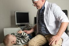 Der Kinderdoktor überprüft die Patienten in seinem Büro Glückliche Kinder sind in einen guten Kinderarzt sehr vernarrt Das Konzep lizenzfreie stockfotografie
