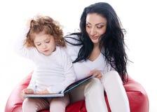 Der Kindergriff ein Buch mit Mutter Lizenzfreie Stockfotos