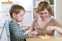 Der Kinderjunge, der mit Bildung spielt, spielt am Tisch im Kindergarten lizenzfreies stockfoto