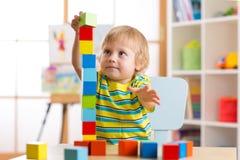 Der Kinderjunge, der mit Block spielt, spielt in Kindertagesstätte Lizenzfreies Stockfoto