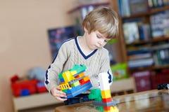 Der Kinderjunge, der mit vielen buntem Plastik spielt, blockiert Innen Stockbilder