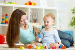 Der Kinderjunge, der Spielwaren bemuttern spielt zusammen lizenzfreie stockbilder