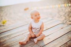 Der Kinderjunge ein Jahr blond sitzt auf einem hölzernen Dock, ein Pier in gestreifter Kleidung, ein Mittel nahe dem Teich auf ei Stockbild