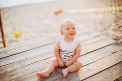 Der Kinderjunge ein Jahr blond sitzt auf einem hölzernen Dock, ein Pier in gestreifter Kleidung, ein Mittel nahe dem Teich auf ei Lizenzfreie Stockbilder