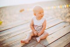 Der Kinderjunge ein Jahr blond sitzt auf einem hölzernen Dock, ein Pier in gestreifter Kleidung, ein Mittel nahe dem Teich auf ei Stockfoto