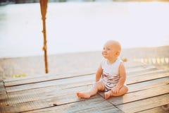 Der Kinderjunge ein Jahr blond sitzt auf einem hölzernen Dock, ein Pier in gestreifter Kleidung, ein Mittel nahe dem Teich auf ei Stockbilder