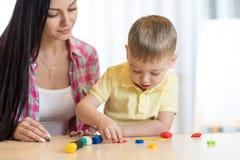 Der Kinderkinderjunge und seine Mutter, die bunten Lehm spielen, spielen an der Kindertagesstätte oder am Kindergarten Stockfoto