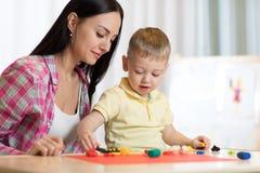 Der Kinderkinderjunge und seine Mutter, die bunten Lehm spielen, spielen an der Kindertagesstätte oder am Kindergarten Lizenzfreie Stockfotografie