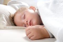 Der kleine blonde Junge, der auf seinem Bett schläft, entspannte sich Stockfoto