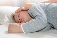 Der kleine blonde Junge, der auf seinem Bett schläft, entspannte sich Stockbilder