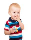 Der kleine blonde Junge in einem gestreiften T-Shirt bedeckte einen Mund Lizenzfreie Stockfotografie