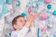 Der kleine blonde Junge fängt Schneeflocken auf dem Hintergrund Weihnachtsbaum feiertage Glückliche Kindheit Stockfotografie