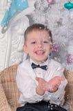 Der kleine blonde Junge fängt Schneeflocken auf dem Hintergrund Weihnachtsbaum feiertage Glückliche Kindheit Lizenzfreie Stockbilder