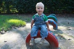 Der kleine blonde Junge im Denimoverall, der auf dem Farbrad sitzt Stockbild