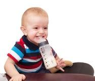 Der kleine blonde Junge lacht und hält mit den Zähnen einen Friedensstifter Lizenzfreie Stockfotos