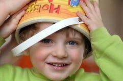 Der kleine blonde Junge mit kleiner grüner Wanne Lizenzfreie Stockfotos