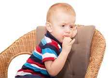 Der kleine blonde Junge runzelte Augenbrauen die Stirn und zerfrisst einen Cracker, Stockbilder